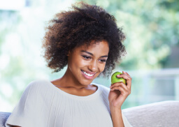 woman smiling and eating an apple